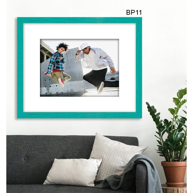 Teal picture frame in living room with white mat and father and son posing in the air